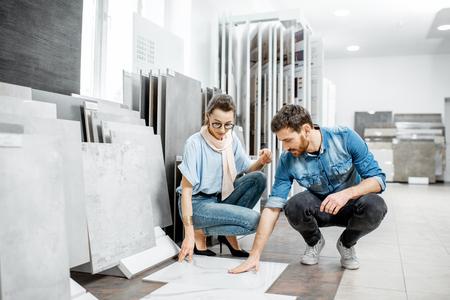 Hermosa joven pareja eligiendo grandes baldosas de granito para la reparación de su casa en el taller de construcción Foto de archivo