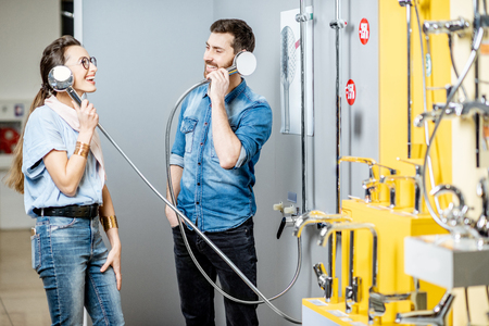 Young couple having fun choosing shower faucet near the showcase of the plumbing shop