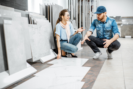 Young woman customer choosing tiles standing with seller or repairman in the ceramic shop