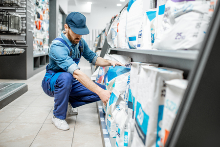 Workman in blue overalls taking a bag with construction mixture, buying materials for repairing in the building supermarket