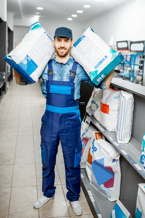 Portrait of a handsome workman in blue overalls holding bags with construction mixture in the building supermarket 版權商用圖片