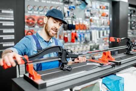 Handsome workman in uniform choosing professional tile cutter in the building shop