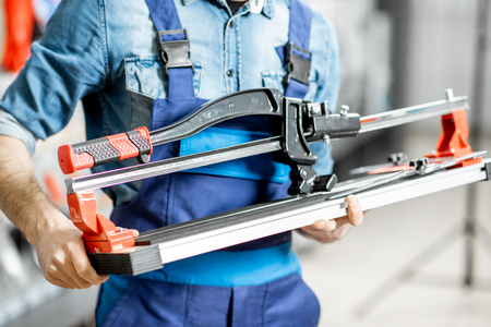 Handsome workman in uniform choosing professional tile cutter in the building shop, close-up view