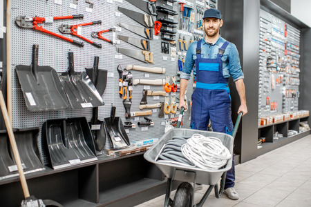 Portrait of a handsome worker in uniform standing with pushcart near the showcase with garden equipment in the shop Reklamní fotografie - 116651085