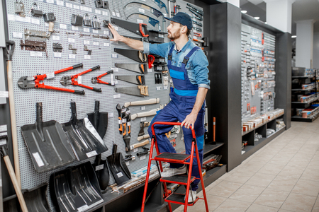 Portrait of a handsome worker in uniform standing on the ladder near the showcase with garden equipment in the shop Stok Fotoğraf