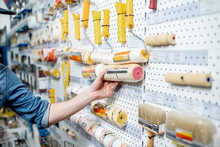 Ouvrier choisissant des outils pour peindre dans l'atelier de construction, vue rapprochée