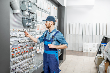 Handsome workman choosing water pipes and pipe joints standing near the showcase in the plumbing shop Stock Photo