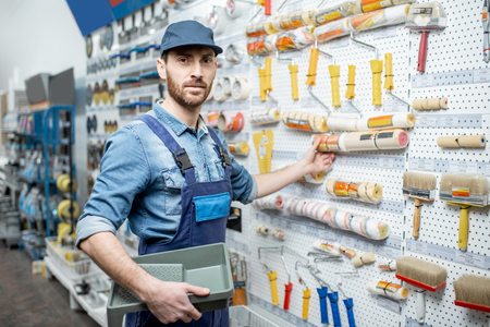 Handsome workman in uniform choosing tools for painting in the building shop Standard-Bild