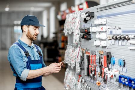 Bel électricien en vêtements de travail choisissant des appareils électriques debout avec un téléphone intelligent dans l'atelier de construction