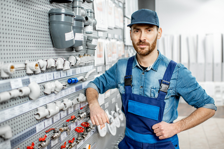 Portrait of a handsome workman choosing water pipes and pipe joints standing near the showcase in the plumbing shop