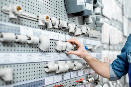 Workman choosing water pipes and pipe joints standing near the showcase in the plumbing shop, close-up view Stock Photo
