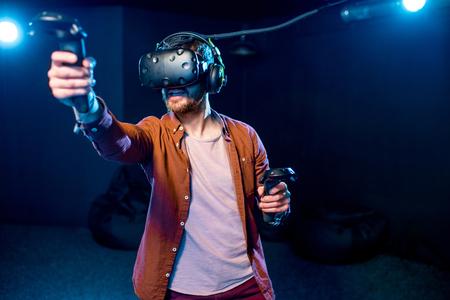 Mężczyzna grający w grę za pomocą zestawu słuchawkowego rzeczywistości wirtualnej i gamepadów w ciemnym pokoju klubu gry