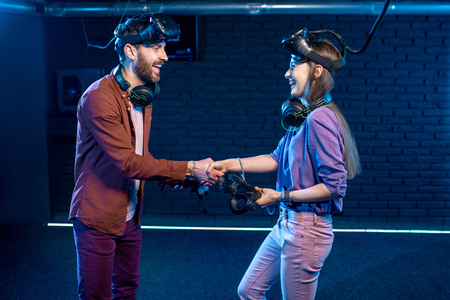 Man and woman shaking hands before the game in virtual reality standing together in the playing club Stock Photo