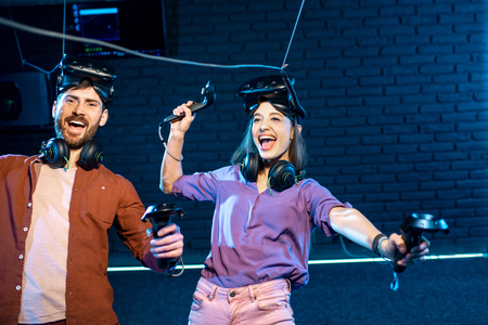 Man and woman simulating weightlessness with virtual reality headset and gamepads in the dark room of the playing club
