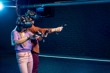 Man and woman playing game using virtual reality headset and gamepads in the dark room of the playing club
