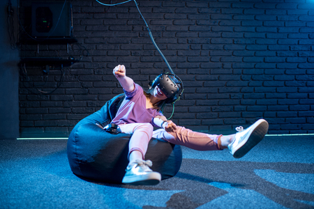 Young woman in virtual reality headset simulating car driving in the dark room of the playing club