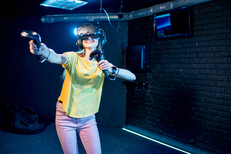 Young woman playing game using virtual reality headset and gamepads in the dark room of the playing club Stock Photo