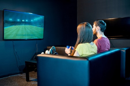 Young couple playing football game with gaming console sitting on the couch at the playing club, back view with tv screen