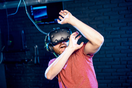 Scared man playing game in virtual reality using VR headset in the playing room
