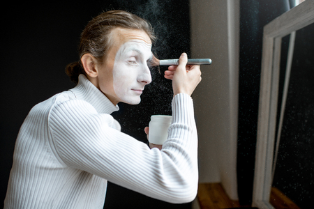 Actor putting mime makeup on his face preparing for perfomence indoors Zdjęcie Seryjne