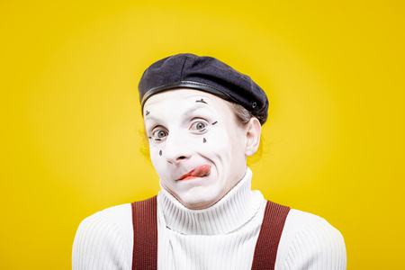 Portrait of an actor as a pantomime with white facial makeup showing expressive emotions on the yellow background indoors Archivio Fotografico