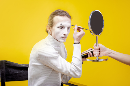 Actor applying facial makeup for pantomime performance sititng in the studio on the yellow background