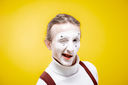 Portrait of an actor as a pantomime with white facial makeup showing expressive emotions on the yellow background indoors Banque d'images - 118134395