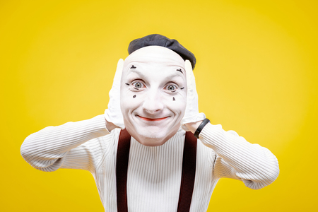 Pantomime actor holding facial mask with positive emotion on the yellow background Stock Photo