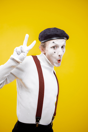 Portrait of an actor as a pantomime with white facial makeup showing expressive emotions on the yellow background indoors Stock Photo
