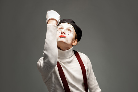 Portrait of a pantomime actor with white facial makeup posing with expressive emotions on the grey background indoors
