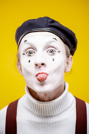 Close-up portrait of an actor as a pantomime with white facial makeup showing expressive emotions on the yellow background indoors Banque d'images - 118134418