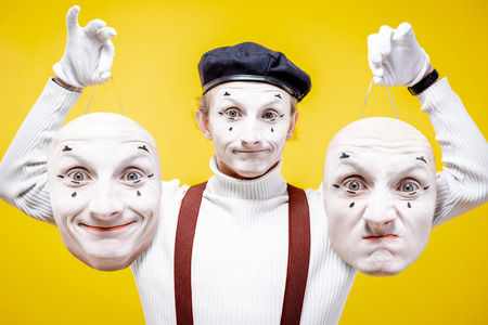 Portrait of a pantoomime holding two facial masks with different emotions on the yellow background. Concept of personality split Stock Photo
