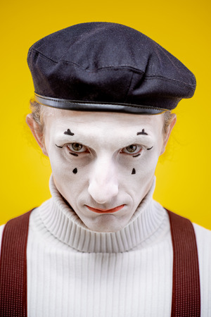 Close-up portrait of an actor as a pantomime with white facial makeup showing expressive emotions on the yellow background indoors Stock Photo