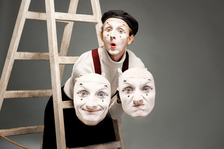 Portrait of a pantoomime actor holding facial masks in the studio with ladder on the grey background Stock Photo