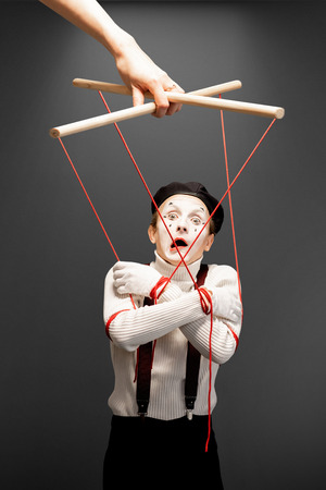 Actor as a marionette controlled with ropes by a huge hand on the grey background. Concept of a human controlling Stock Photo