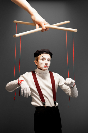 Actor as a marionette controlled with ropes by a huge hand on the grey background. Concept of a human controlling 版權商用圖片