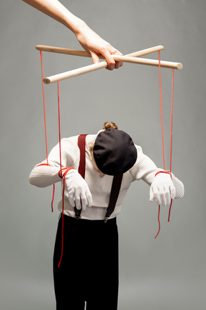 Actor as a marionette controlled with ropes by a huge hand on the grey background. Concept of a human controlling Foto de archivo