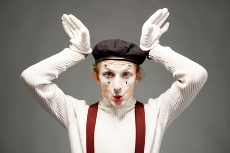 Portrait of a pantomime actor with white facial makeup posing with expressive emotions on the grey background indoors Banque d'images - 118134512
