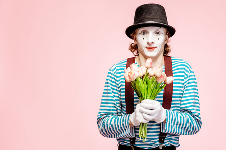 Emotional pantomime posing with tulip bouquet on the pink background indoors. Valentines Day and love concept