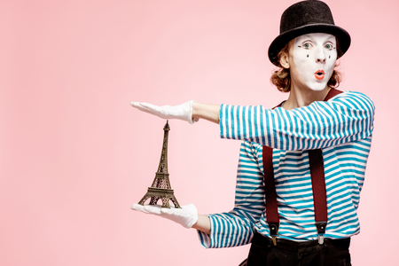 Pantomime with white facial makeup posing with Eiffel tower on the pink background. French mime concept