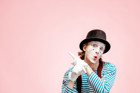 Emotional pantomime with white facial makeup showing empty space of the pink background, advertising something