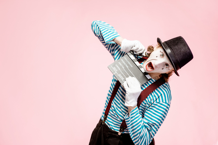 Portrait of an actor as a pantomime with cinematography clapperboard on the pink background