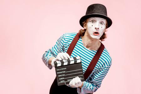 Portrait d'un acteur en pantomime avec clap de cinéma sur fond rose
