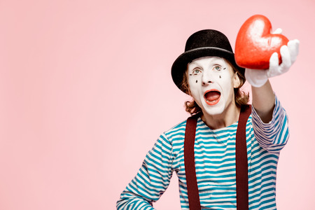 Portrait of an actor as a pantomime with white facial makeup posing with red heart on the pink background