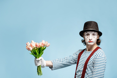 Emotional pantomime posing with tulip bouquet on the blue background indoors. Valentines Day and love concept Banque d'images - 118134566