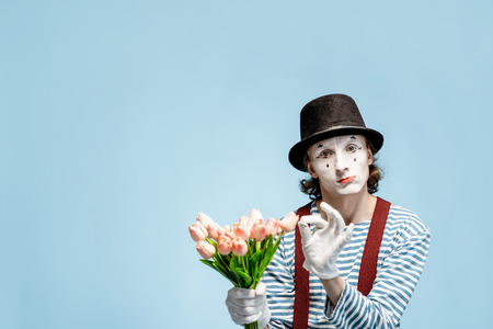 Emotional pantomime posing with tulip bouquet on the blue background indoors. Valentines Day and love concept