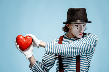 Portrait of an actor as a pantomime with white facial makeup posing with red heart on the blue background
