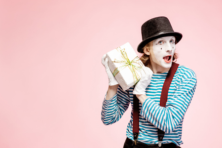 Portrait of an actor as a pantomime with white facial makeup posing with gift box on the pink background