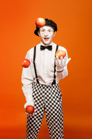 Portrait of an actor as a pantomime with white facial makeup showing expressive emotions on the orange background in the studio