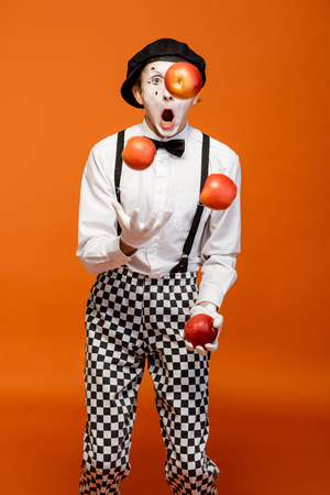 Portrait of an actor as a pantomime with white facial makeup showing expressive emotions on the orange background in the studio 写真素材 - 118134713
